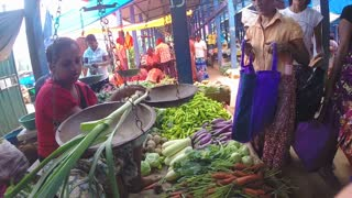 HIKKADUWA, SRI LANKA - MARCH 2014: View of woman weighing her fresh vegetables at the Sunday market in Sri Lanka.