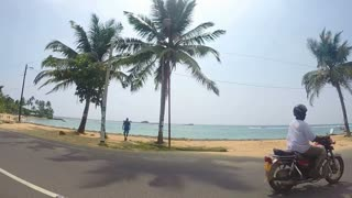 HIKKADUWA, SRI LANKA - MARCH 2014: View on the beautiful beach with palm trees from moving vehicle.
