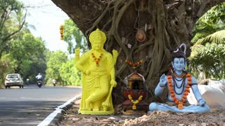 Hindu statues by tree at the city road in Goa, with vehicles passing.