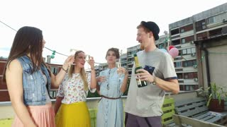 Hipster man toasting and drinking champagne with beautiful female friends