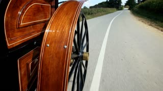 Horse drawn carriage wheel spinning on road