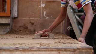 Indian boy realigning sand with a trowel at street in Jodhpur.