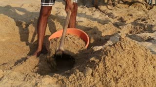 Indian man collecting sand in bowl at beach.