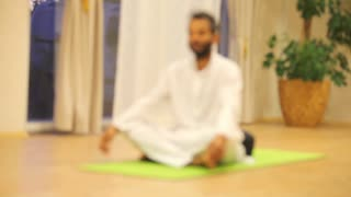 Indian man sitting on green mat and practicing yoga
