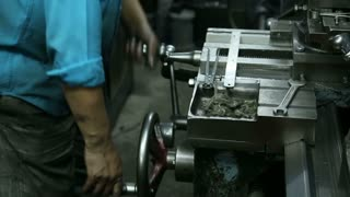 Indian man turning the parts of machine in workshop in Jodhpur.