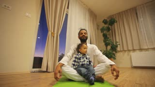 Indian man with kid practicing yoga