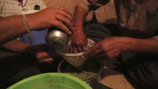 Indian men filtering liquid ingredient through a sieve.