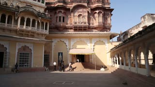 JODHPUR, INDIA - 10 FEBRUARY 2015: Man passing through courtyard and people entering building at Mehrangarh fort.