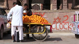 JODHPUR, INDIA - 10 FEBRUARY 2015: Men working at street stand with citrus fruit in Jodhpur.