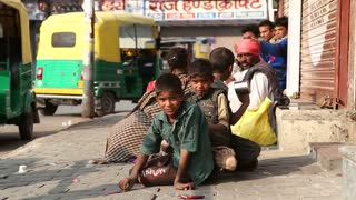 JODHPUR, INDIA - 11 FEBRUARY 2015: Boys playing at street in Jodhpur with people sitting and passing in background.