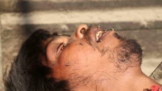 JODHPUR, INDIA - 11 FEBRUARY 2015: Flies on face of sleeping Indian man laying at street in Jodhpur, closeup.