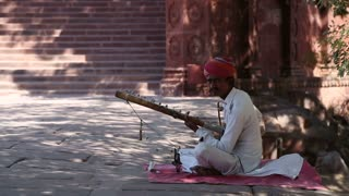 JODHPUR, INDIA - 11 FEBRUARY 2015: Indian man playing music on string instrument at street in Jodhpur.