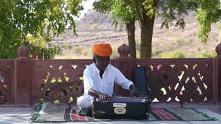 JODHPUR, INDIA - 11 FEBRUARY 2015: Indian man playing on traditional instrument at patio in Jodhpur.