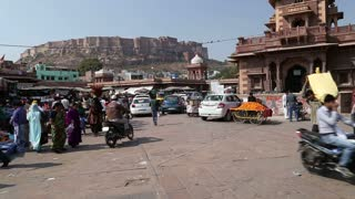 JODHPUR, INDIA - 11 FEBRUARY 2015: People and vehicles passing down the street beneath Mehrangarh fort.