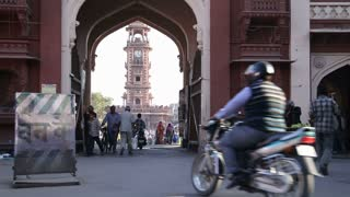 JODHPUR, INDIA - 11 FEBRUARY 2015: People and vehicles passing under street arc, with view on tower in background.