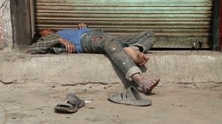 JODHPUR, INDIA - 11 FEBRUARY 2015: Sleeping Indian man laying at street in Jodhpur.