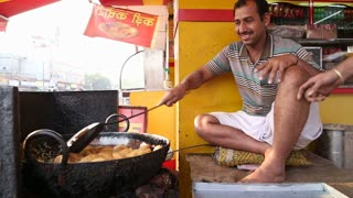 JODHPUR, INDIA - 11 FEBRUARY 2015: Smiling Indian man frying local food at street stand in Jodhpur.