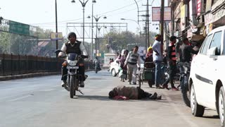 JODHPUR, INDIA - 11 FEBRUARY 2015: Vehicles and people passing by the man sleeping at street in Jodhpur.