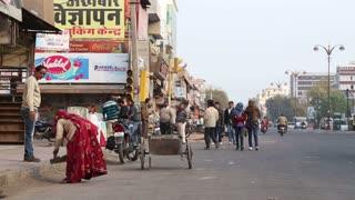 JODHPUR, INDIA - 11 FEBRUARY 2015: Woman preparing to ride wheelbarrow down the street in Jodhpur.