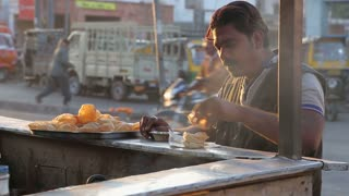 JODHPUR, INDIA - 12 FEBRUARY 2015: Indian man eating local food prepared at market stand in Jodhpur.