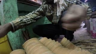 JODHPUR, INDIA - 12 FEBRUARY 2015: Man arranging small ceramic cups under a table at market in Jodhpur.