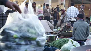 JODHPUR, INDIA - 12 FEBRUARY 2015: Person taking away bag of vegetables, with people talking at market in Jodhpur.