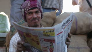 JODHPUR, INDIA - 12 FEBRUARY 2015: Portrait of smiling Indian man sitting and reading newspaper.