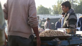 JODHPUR, INDIA - 12 FEBRUARY 2015: Steam coming out of jar surrounded by pile of Indian nuts at market stand.