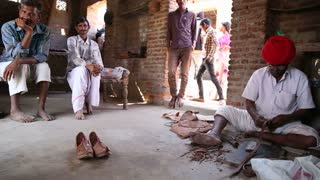 JODHPUR, INDIA - 13 FEBRUARY 2015: Group of Indian men sitting in house and standing at doorstep.