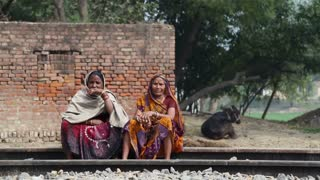 JODHPUR, INDIA - 13 FEBRUARY 2015: Local women sitting at railway, with donkey lying on ground in background.