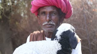 JODHPUR, INDIA - 13 FEBRUARY 2015: Portrait of local Indian man with turban holding a lamb in his hands.