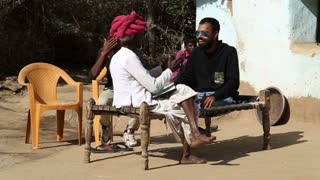 JODHPUR, INDIA - 13 FEBRUARY 2015: Young and old Indian man sitting on bench and cheerfully talking.