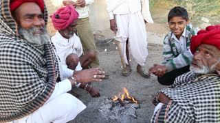 JODHPUR, INDIA - 14 FEBRUARY 2015: Group of local Indian men warming their hands by fire on the ground, closeup.