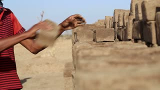 JODHPUR, INDIA - 14 FEBRUARY 2015: Indian men building a row of bricks at field in Jodhpur.