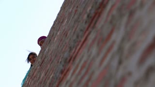 JODHPUR, INDIA - 14 FEBRUARY 2015: Low angle view of young girls peeking from the top of a wall.