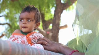 JODHPUR, INDIA - 14 FEBRUARY 2015: Portrait of Indian baby boy sitting while his mother holds him.