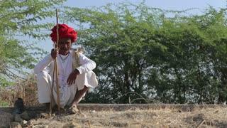 JODHPUR, INDIA - 14 FEBRUARY 2015: Portrait of local Indian man sitting by a village road in Jodhpur.