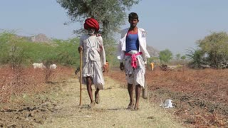 JODHPUR, INDIA - 14 FEBRUARY 2015: Two local Indian cattle keepers walking down the road by a field in Jodhpur.