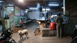 JODHPUR, INDIA - 17 FEBRUARY 2015: Dog barking while men are preparing chai at street shop in Jodhpur.
