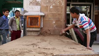 JODHPUR, INDIA - 17 FEBRUARY 2015: Indian boy realigning sand with a trowel at street in Jodhpur.