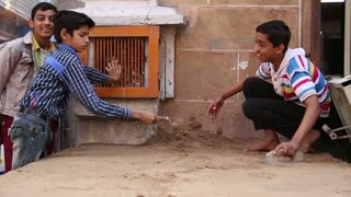 JODHPUR, INDIA - 17 FEBRUARY 2015: Indian boys realigning sand with a trowel at street in Jodhpur.