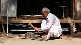 JODHPUR, INDIA - 17 FEBRUARY 2015: Indian man shaping rod at the street while vehicles and people pass.