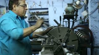 JODHPUR, INDIA - 17 FEBRUARY 2015: Indian man working on a machine in workshop in Jodhpur, closeup.