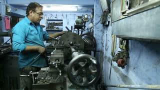 JODHPUR, INDIA - 17 FEBRUARY 2015: Indian man working on a machine in workshop in Jodhpur.