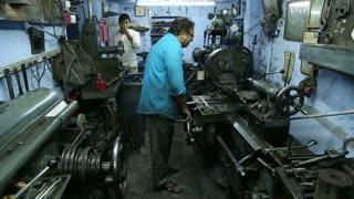 JODHPUR, INDIA - 17 FEBRUARY 2015: Indian men working on machines in small workshop in Jodhpur.
