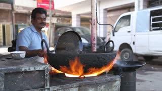 JODHPUR, INDIA - 5 FEBRUARY 2015: Indian man smiles while cooking samosas.