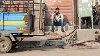 JODHPUR, INDIA - 5 FEBRUARY 2015: Man sitting on the stairs at street with mobile phone.