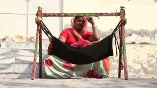 JODHPUR, INDIA - 5 FEBRUARY 2015: Woman swinging child in cradle.