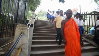 KANDY, SRI LANKA - FEBRUARY 2014: Buddist monk descending stairs in Kandy. Kandy is a major city in Sri Lanka, second biggest after Colombo.