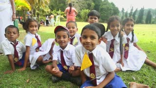 KANDY, SRI LANKA - FEBRUARY 2014: Group of Sri Lankan children in school uniform playing in the Botanical Gardens. All children are required to wear uniforms.